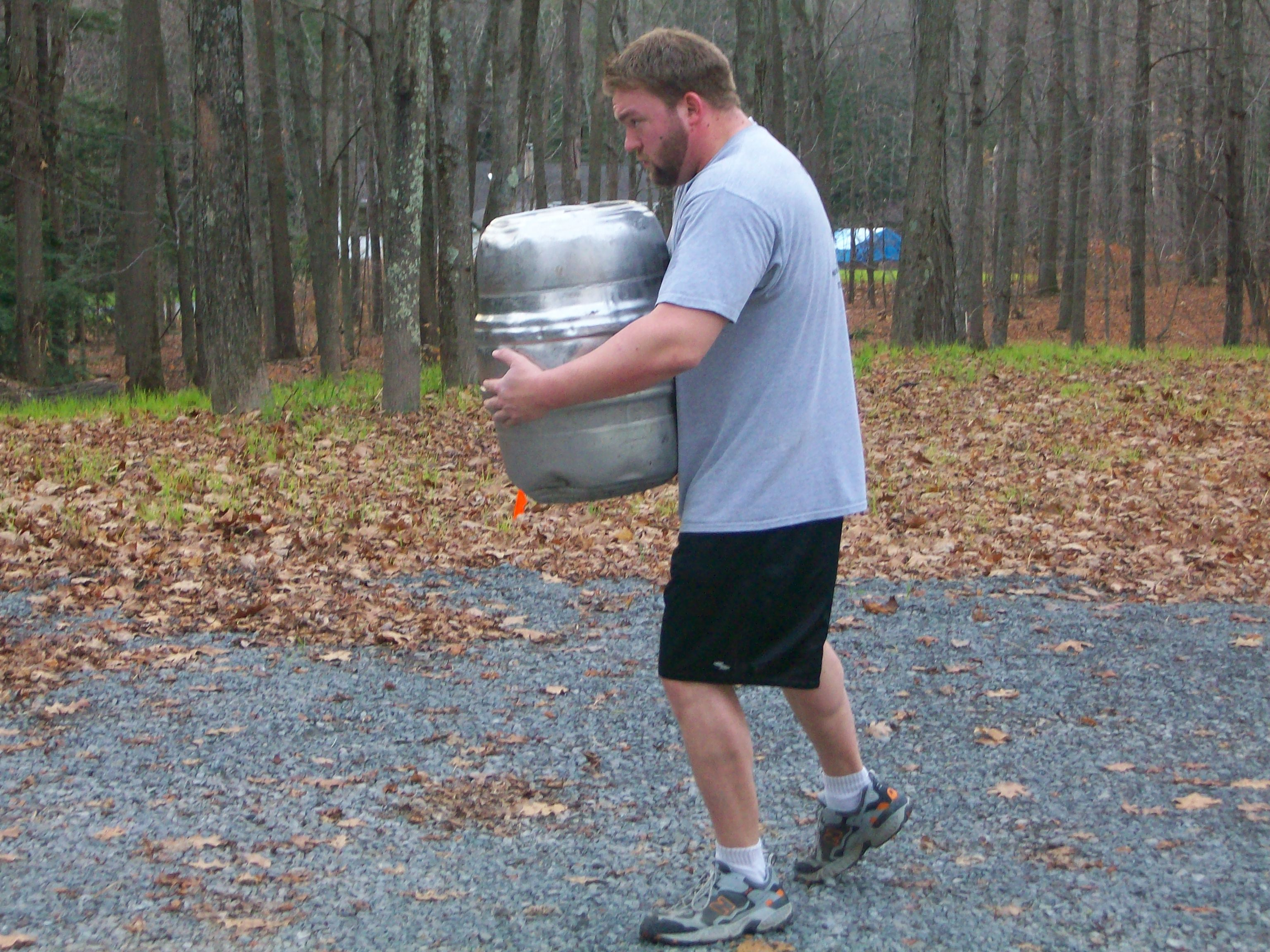 Man carrying keg and walking in woods.